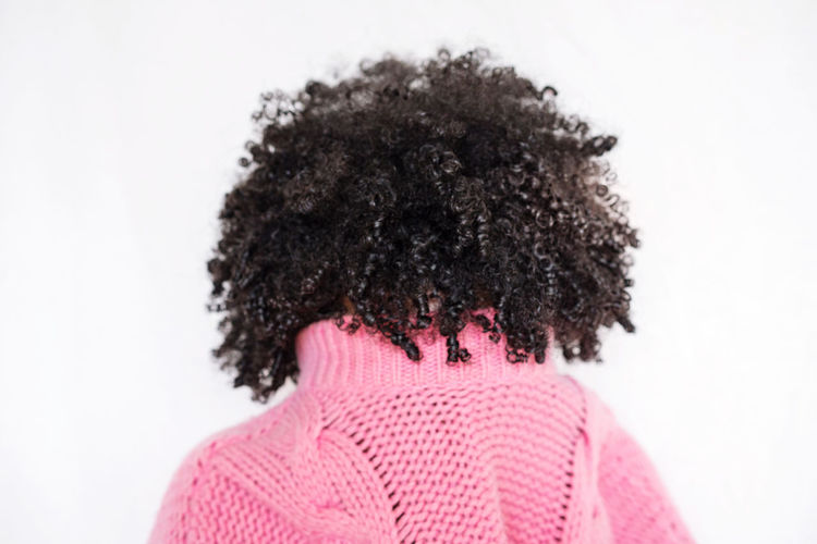 Black woman with afro wearing colorful jumper