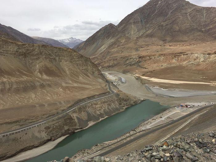 where the emerald waters of river Indus meet the muddy waters of the Zanskar river in Ladakh , India Barren Indus River Ladakh Meeting Point Mountains Sky Two Waters Water Zanskar And Indus Rivers Zanskar River