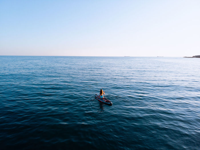 Woman on stand up paddle board, woman paddling on sup board and enjoying turquoise transparent water