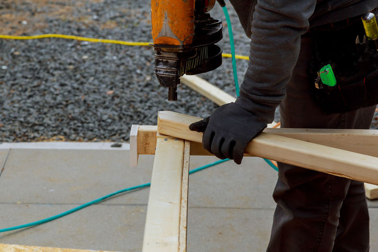 Midsection of man using nail gun on woods at construction site