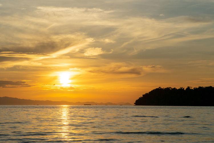 Landscape of calm sea with silhouette of island and orange light of sunrise