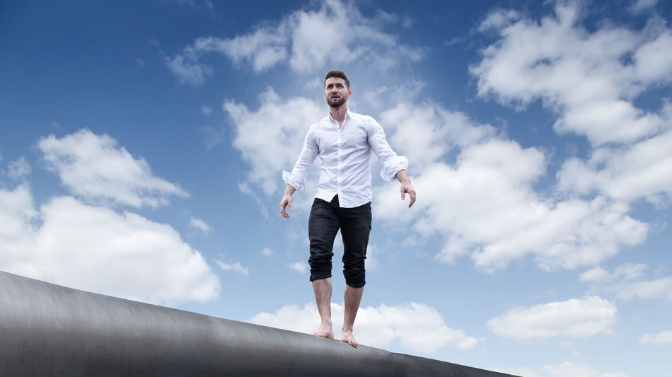 Attractive businessman is balancing barefoot on a wall Casual Cloud Freedom Happy RISK Balanced Barefoot Bearded Businessman Career Casual Clothing Cloud - Sky Crazy Full Length Intelligence Leisure Activity Lifestyles Male Nature One Person Outdoors People Smiling Successful Young Adult