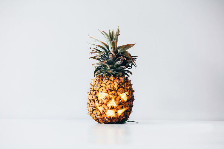 Close-up of pineapple on table against white background