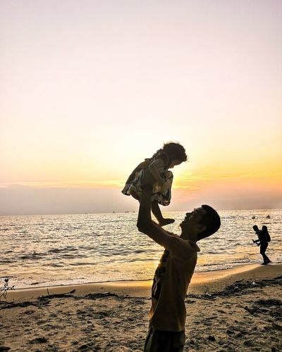 Side view of man holding aloft baby girl at beach during sunset