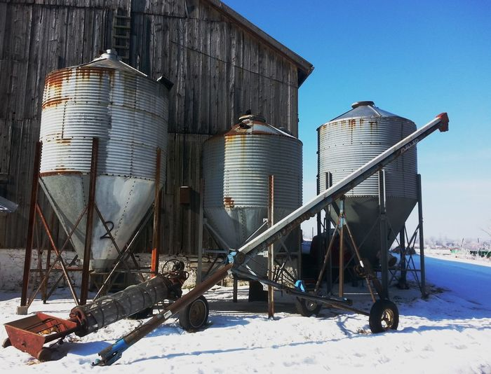 Rusty silos on snow covered field
