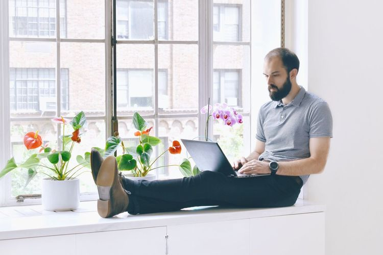 Man using laptop while sitting by window at home