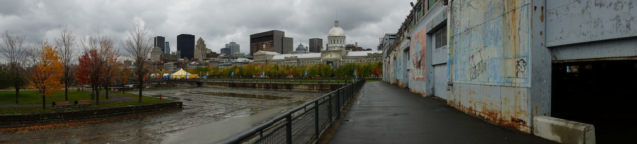 Panoramic view of wet street amidst buildings against sky