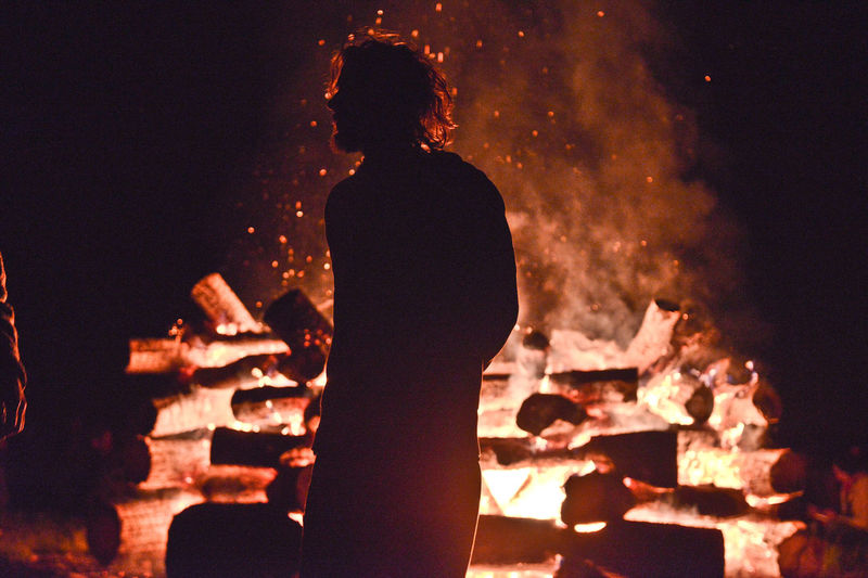 Silhouette man standing against bonfire at night