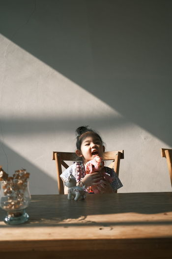 Cute girl sitting on table at home