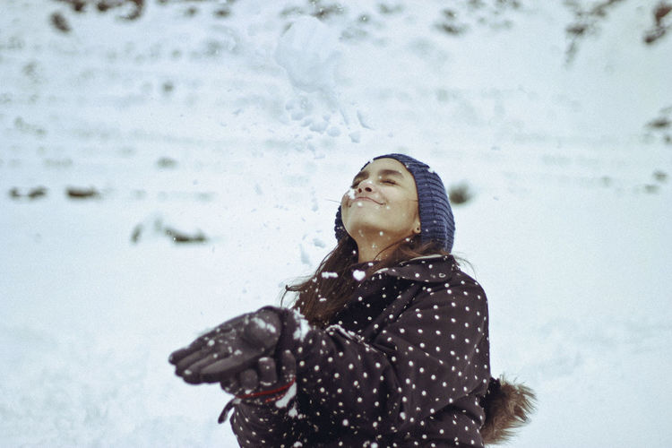 Woman In Warm Clothing Playing With Snow