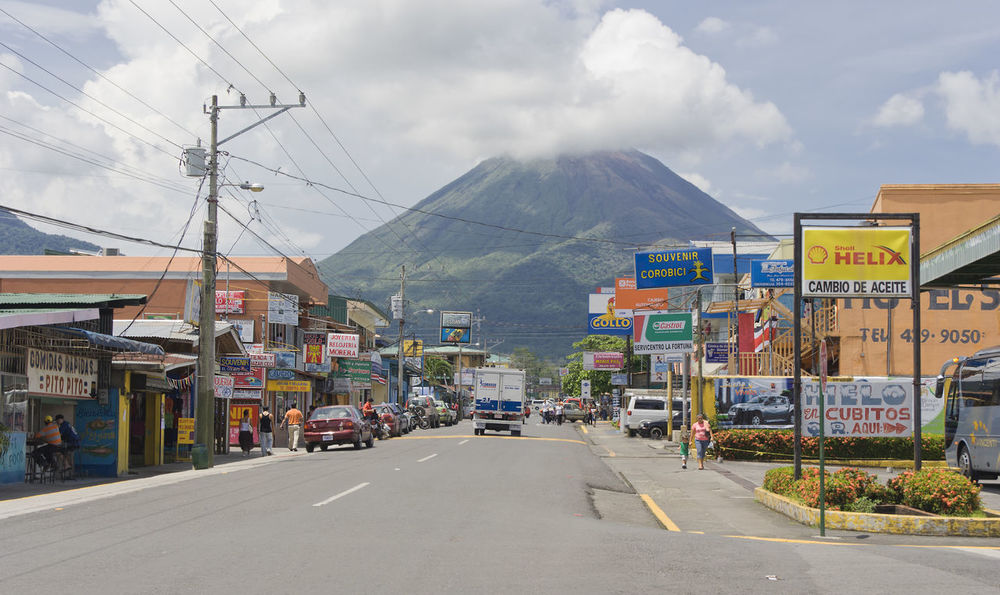 Traffic and Volcano Arenal in Costa Rica Advertisement Alajuela Arenal  Arenal Volcano Billboard Building Building Exterior Business City Cityscape Commerce Costa Rica Highway Mountain People Perspective Poverty Retail  Social Issues Store Street Traffic Travel Destinations Urban Volcano
