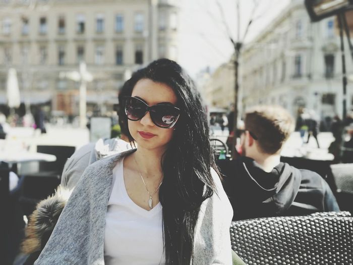 Beautiful Woman Wearing Sunglasses While Sitting On Chair At Sidewalk Cafe
