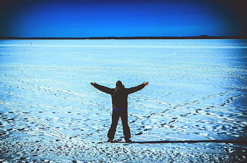 Real People Arms Outstretched Arms Raised Water One Person Lifestyles Standing Nature Beauty In Nature Scenics Tranquil Scene Outdoors Sea Horizon Over Water Leisure Activity Day Women Blue Full Length Sky Finland Ice Age
