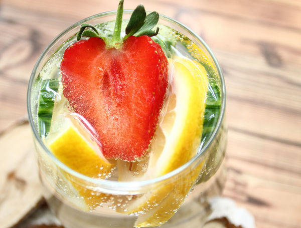 Detox flavored water with lemon, cucumber and strawberry on white background with decoration. Healthy food concept. Refreshing summer homemade cocktail. Copy space. No sharpen. Aromatherapy Boost Cleaning Cocktail Cucumber Detox Diet Freshness Antioxidant Beauty Beauty In Nature Beauty In Glass Glass Glass Of Water With Lemon Healthy Eating Healthy Food Healthy Lifestyle Lemon Loss Weight Metabolism Organism Refreshing Strawberry Summer Water