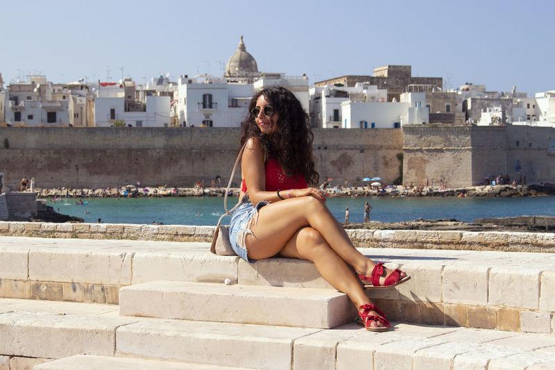 Fashionable Woman Sitting On Retaining Wall