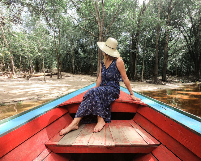 Woman sitting in boat against trees