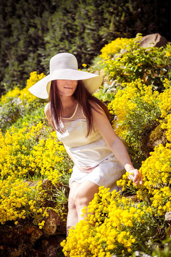 Young woman with yellow flowers in park