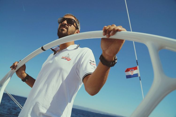 EyeEm Selects EyeEm Selects Sunglasses Low Angle View Clear Sky Blue Sky Patriotism Day One Person Pride Sailor Standing Sunlight Sea Real People Nautical Vessel Men Yacht Young Adult One Man Only