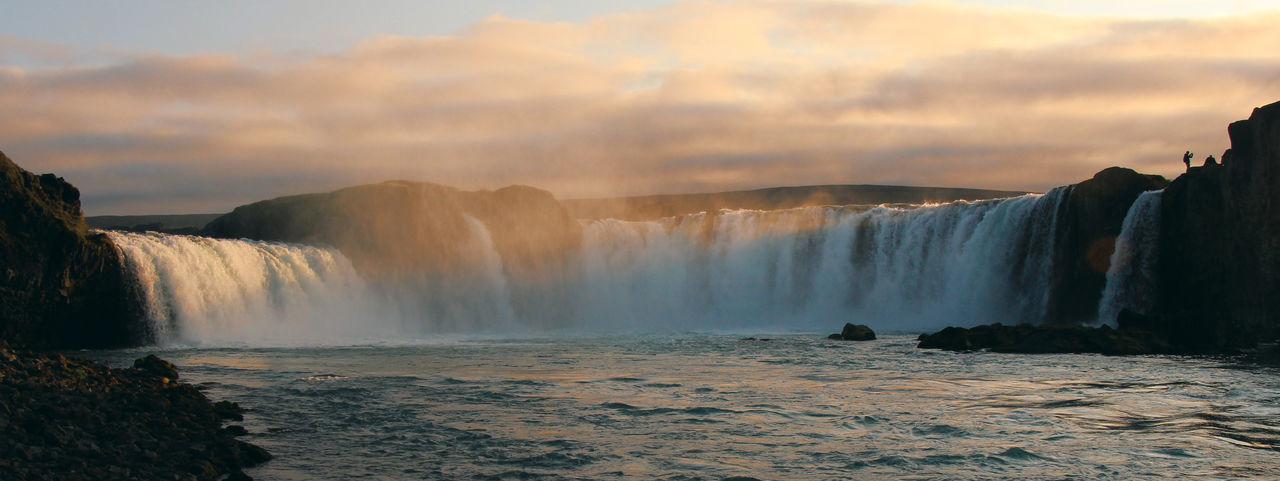 Scenic view of waterfall against cloudy sky at sunset