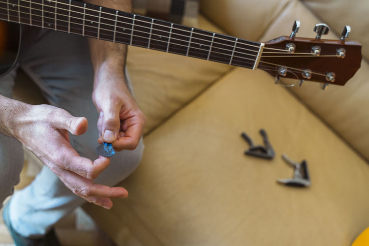 Midsection of man preparing guitar in home