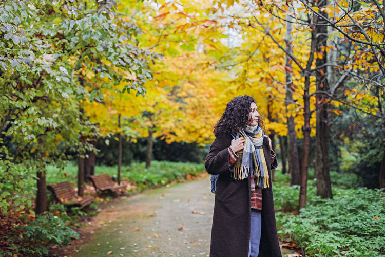 Woman standing by trees in forest during autumn