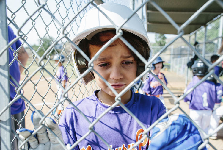 Portrait of teenage boy seen through chainlink fence