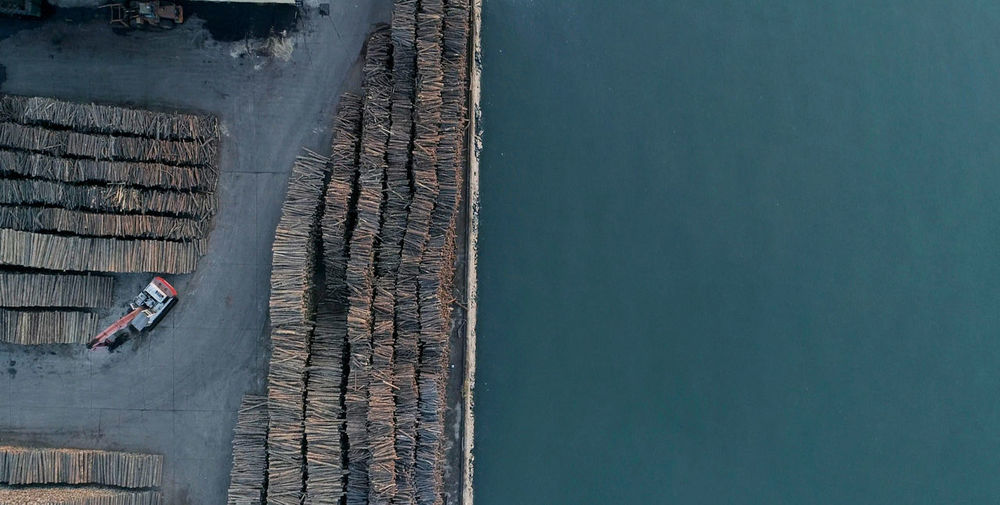 Stacked woods by the sea Aerial View Architecture Built Structure Copy Space Day High Angle View Men Mode Of Transportation Nature Nautical Vessel Occupation One Person Outdoors Real People Sea Swimming Pool Transportation Water Waterfront