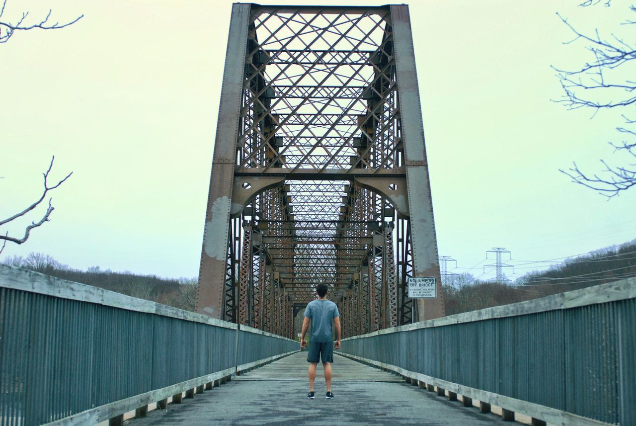 rear view, architecture, walking, bridge - man made structure, full length, real people, one person, built structure, day, men, the way forward, outdoors, lifestyles, tree, building exterior, clear sky, sky, nature, people