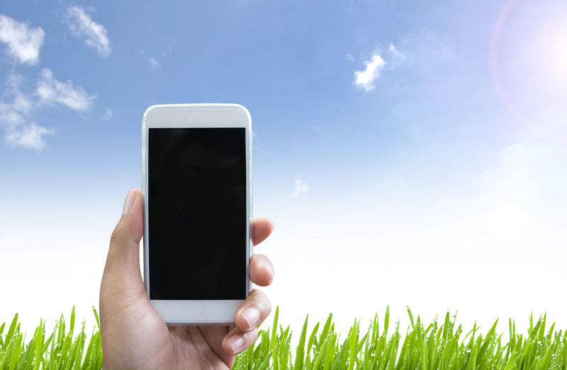 Cropped Hand Of Person Holding Smart Phone On Field Against Sky