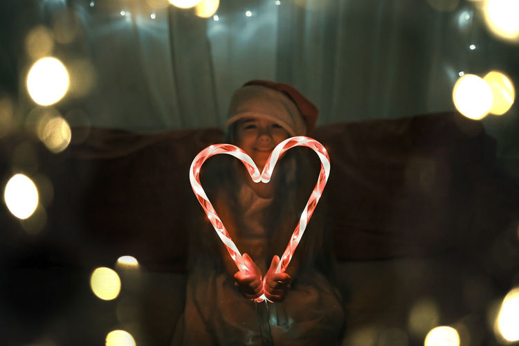 Girl making heart shape of illuminated candy canes on sofa in darkroom