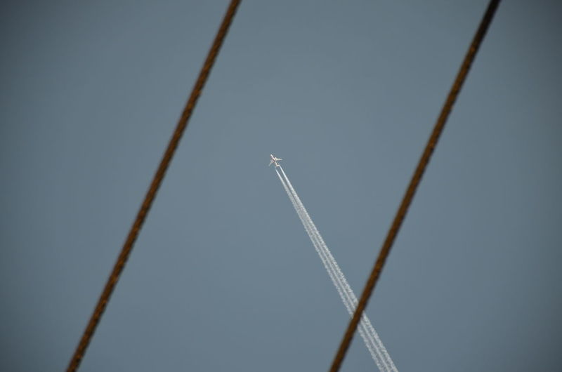 Low angle view of airplane flying against clear sky seen amidst cables