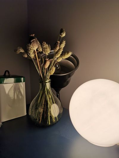 Close-up of vase on table against wall at home