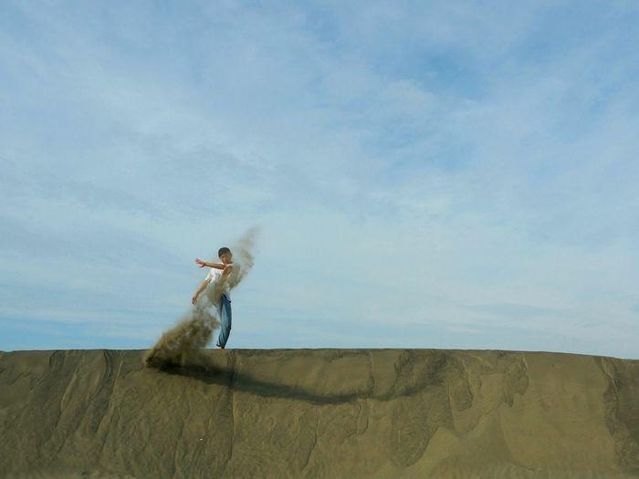 Man standing on desert against sky