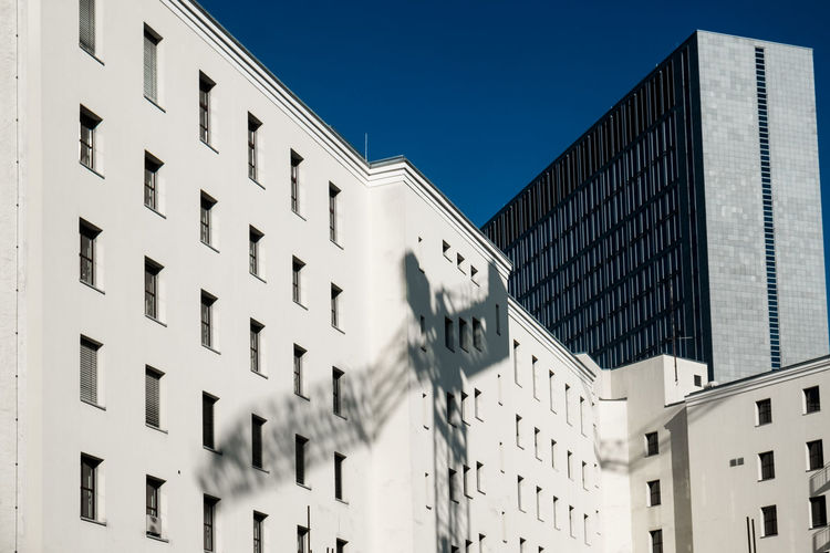 Shadow of crane on building during sunny day
