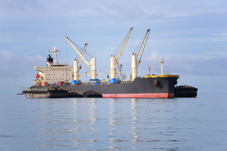 Small passenger boat running in the sea and have cargo ship on daytime. Water Nautical Vessel Transportation Sea Waterfront Ship Sky Freight Transportation Business Nature Shipping  Mode Of Transportation Industry No People Cloud - Sky Container Ship Crane - Construction Machinery Day Outdoors