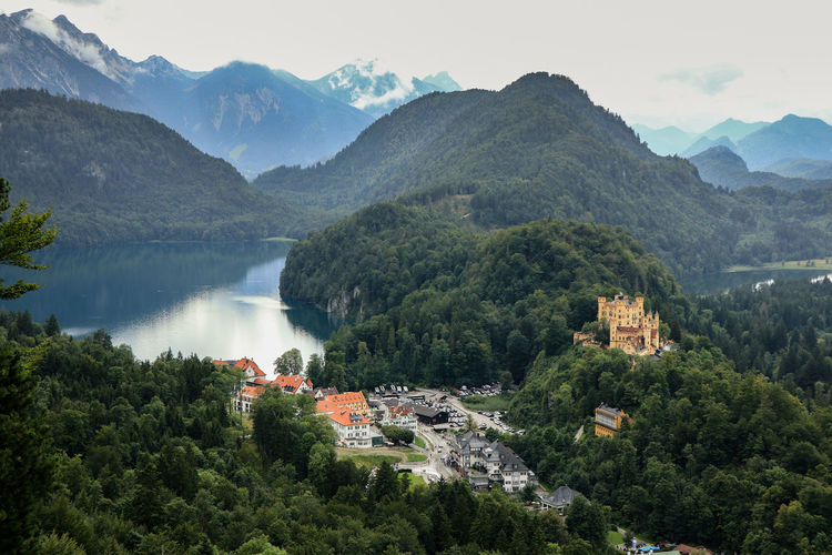 Hohenschwangau castle scenic view of townscape by mountains against sky