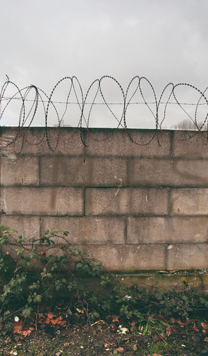 View of barbed wire fence against wall