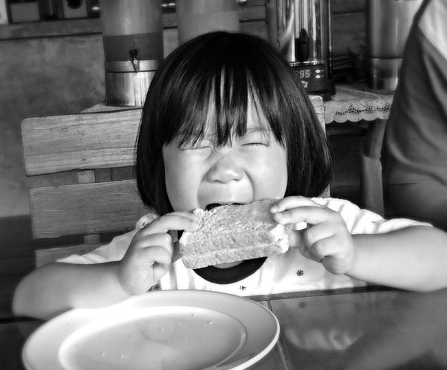 Portrait of cute child eating sandwich