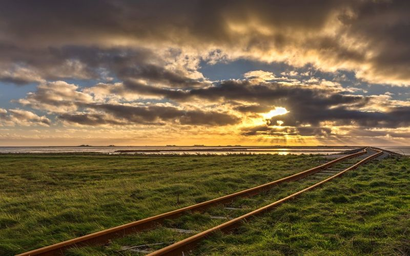 Railroad tracks on field against cloudy sky during sunset