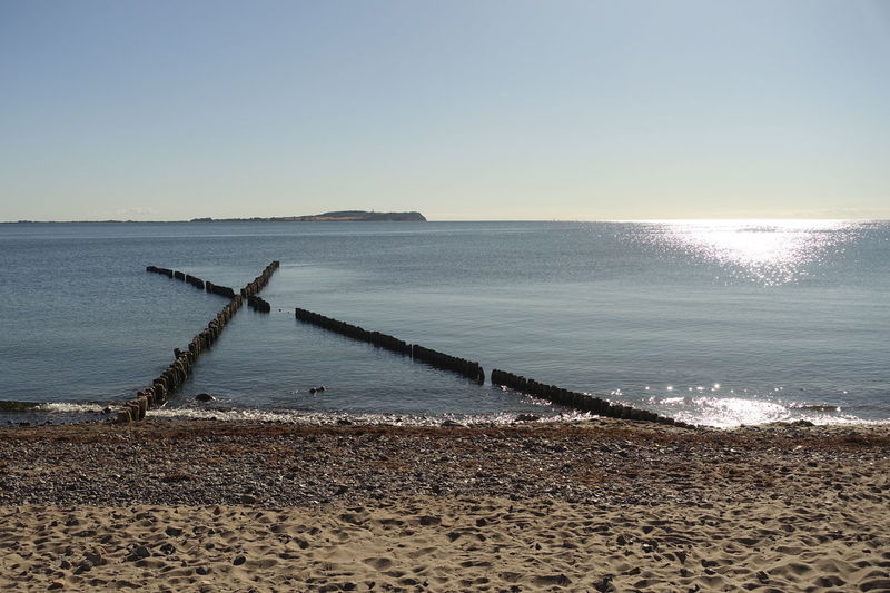 Baltic Sea Sunlight View To The Island Hiddensee Beach Beauty In Nature Breakwaters Clear Sky Day Horizon Horizon Over Water Idyllic Land Nature No People Non-urban Scene Outdoors Scenics - Nature Sea Sky Sunlight Tranquil Scene Tranquility Travel Destination Water