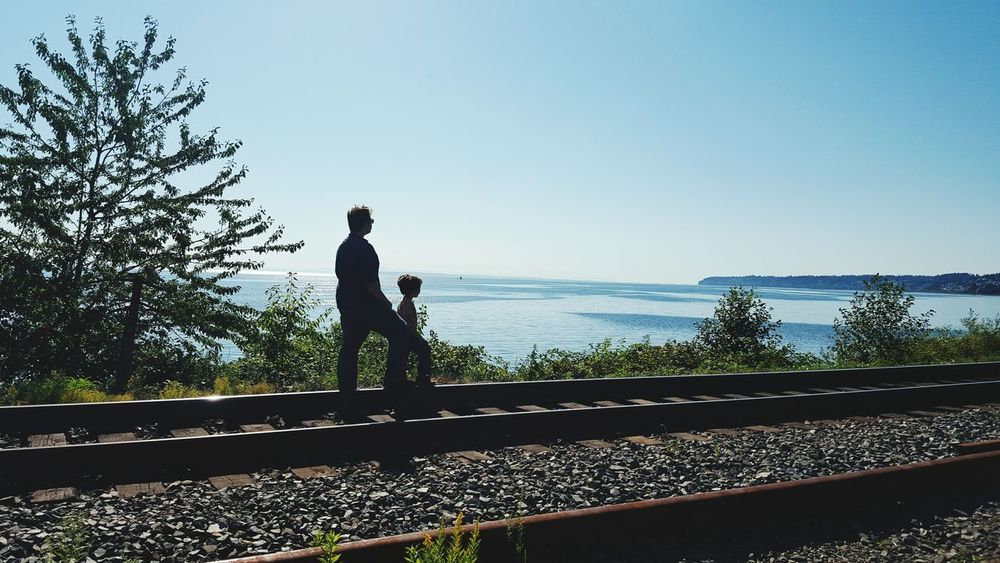 """Brothers looking over at Canada."" Pacific Northwest  Water People Train Tracks Silhouette Photography JessCarrieA"