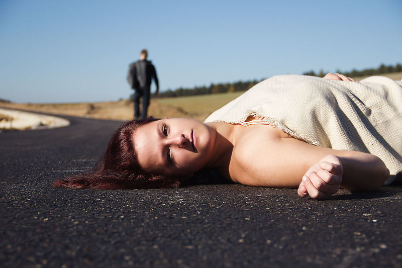 Portrait of young woman lying down on road against clear sky
