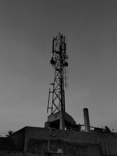 Low angle view of communications tower against clear sky