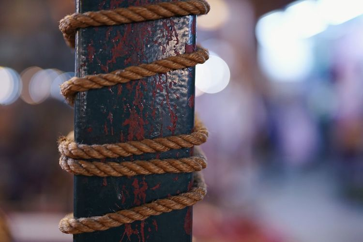 Close-up of rope tied up on rusty metal