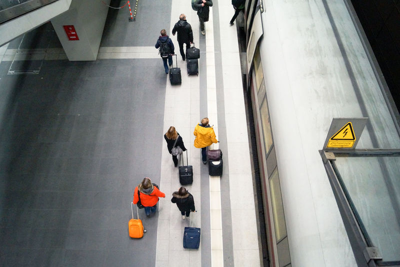High angle view of people carrying luggage on railroad station platform