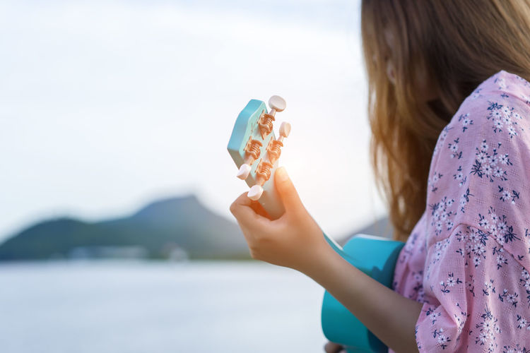 Midsection of woman playing ukulele by lake against sky