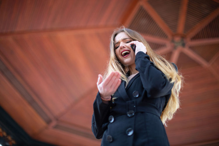 Beautiful young female in elegant outfit screaming and gesturing while being fired from work by phone in park Woman Argue Fired Work Smartphone Screaming Young Angry Gesturing Conversation Business Stress Talking Displeased Mad Yelling Shouting Female Gazebo Park Job Bad Call Corporate Employee