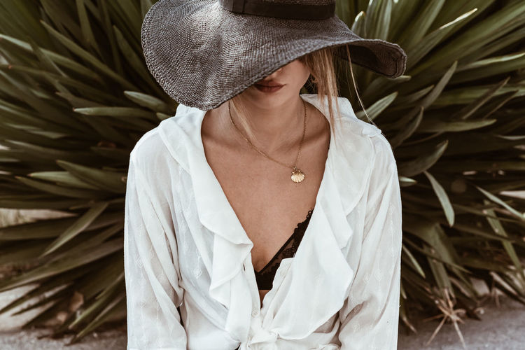 Hat One Person Clothing Leisure Activity Lifestyles Real People Women Front View Standing Casual Clothing Adult Focus On Foreground Day Waist Up Young Adult Looking White Color Nature Plant Outdoors Obscured Face