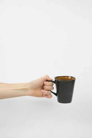 Hand holding coffee cup against white background