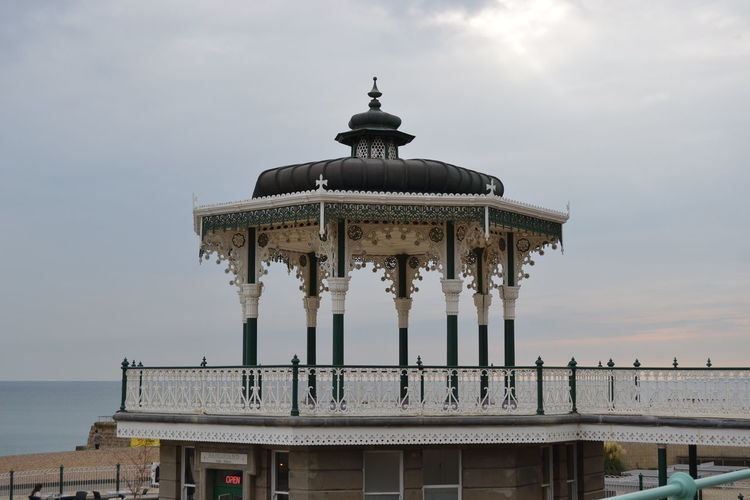 Low angle view of brighton palace pier against cloudy sky